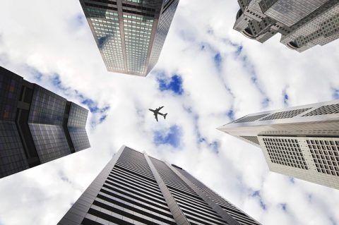airplane fly over; city buildings